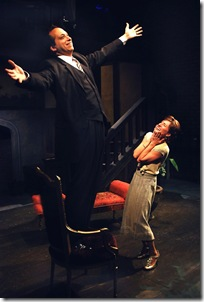 "Lord Peter Wimsey (Peter Greenberg; left; standing on chair) expresses his joy at finally being wed to Harriet Vane (Jenifer Tyler; right), in Lifeline Theatre's world premiere production of ""Busman's Honeymoon,"" adapted by Frances Limoncelli, directed by Paul S. Holmquist, based on the classic mystery by Dorothy L. Sayers."
