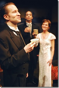 "Bunter (Phil Timberlake; left foreground; holding teacup) offers a toast to his employers, Lord Peter Wimsey (Peter Greenberg; center background) and Harriet Vane (Jenifer Tyler; right background; white dress), on their wedding night, in Lifeline Theatre's world premiere production of ""Busman's Honeymoon,"" adapted by Frances Limoncelli, directed by Paul S. Holmquist, based on the classic mystery by Dorothy L. Sayers"