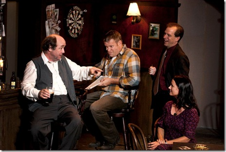 from left, Jack (Brad Armacost), Jim (Jeff Christian), and Finbar (Kevin Theis), try to curry favor with Valerie (Sarah Wellington) by sharing betting tips, in Seanachaí Theatre Company's THE WEIR by Conor McPherson. Photograph courtesy of Eileen Molony.