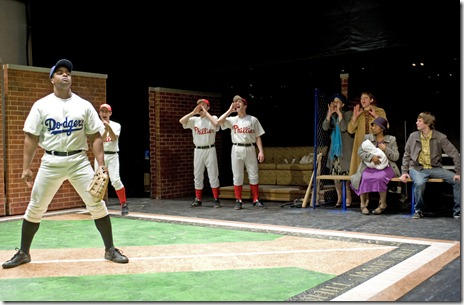 Pictured (far left) Kamal Angelo Bolden as Jackie Robinson, (seated, with baby) Tracey Bonner as Rachel Robinson, and (far right) Tyler Ross as Joey Stoshack. Photo credit:  Michael Brosilow
