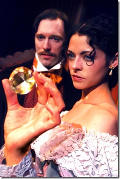 "Rachel Verinder (Ann Sonneville, right) and Franklin Blake (Cody Proctor, left) admire the legendary Moonstone, an Indian diamond with a dark history; in Lifeline Theatre's world premiere production of ""The Moonstone,"" adapted by Robert Kauzlaric, directed by Paul S. Holmquist and based on the classic mystery by Wilkie Collins. Photo by Suzanne Plunkett."