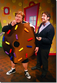 "Mr. Bing (Anthony Kayer, right) and Arnie the doughnut (Brandon Paul Eells, left) negotiate a new relationship between man and doughnut; in Lifeline Theatre's production of ""Arnie the Doughnut,"" adapted by Frances Limoncelli, music by George Howe, and directed by Elise Kauzlaric, based on the popular children's book by Laurie Keller Photo by Suzanne Plunkett."