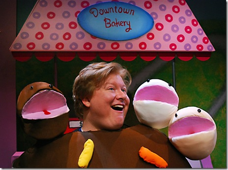 "Arnie the doughnut (Brandon Paul Eells, right) meets his new doughnut-hole friends at the Downtown Bakery; in Lifeline Theatre's production of ""Arnie the Doughnut,"" adapted by Frances Limoncelli, music by George Howe, and directed by Elise Kauzlaric, based on the popular children's book by Laurie Keller. Photo by Suzanne Plunkett."