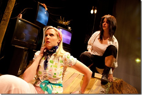 L to R: Melanie (Heather Townsend) stumbles into Trevor's (Lucy Carapetyan) studio in the woods in Dog & Pony Theatre Company's Midwest premiere production of Roadkill Confidential May 4-June 4 at The Building Stage. Photo by Timmy Samuel.